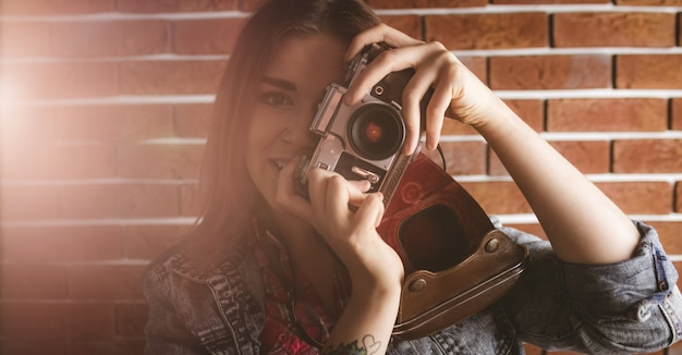 Femme, photographier, depuis, appareil photo vintage, contre, mur brique