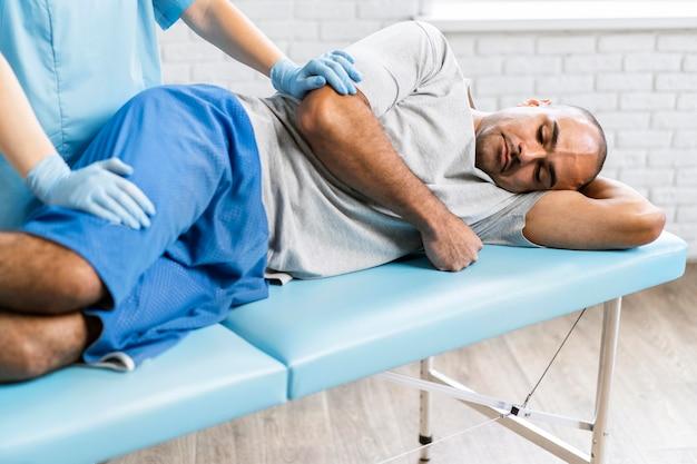 Femme physiothérapeute contrôle patient masculin