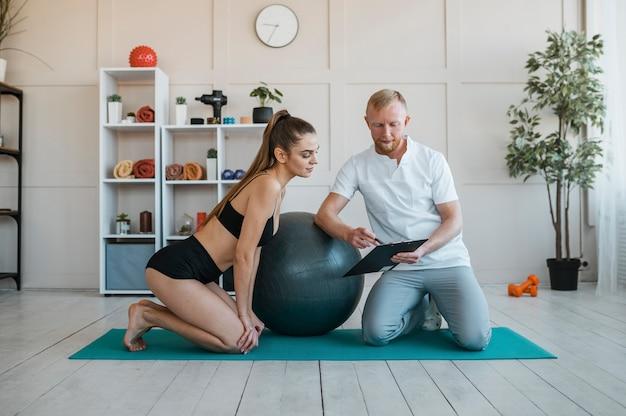 Femme avec physiothérapeute, faire des exercices avec ballon