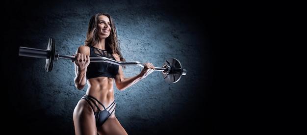 Femme de physique athlétique posant en studio avec une barre dans ses mains