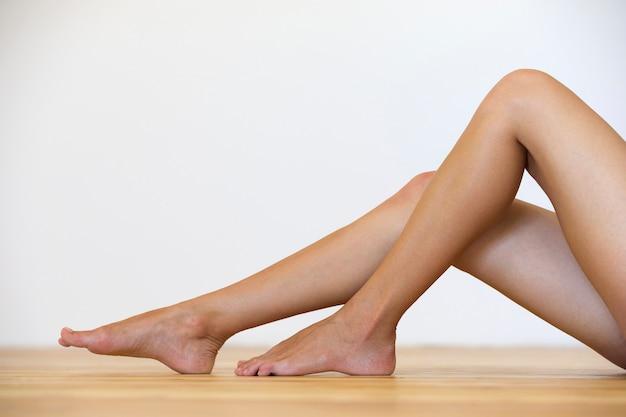 Femme pieds nus sur le sol. soins des jambes et concept de traitement de la peau.