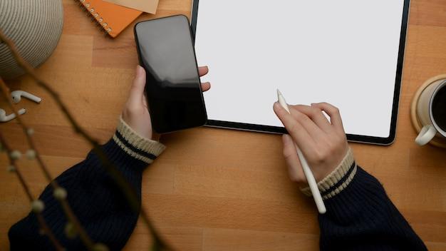Femme pigiste main gauche tenant le smartphone et main droite travaillant avec tablette