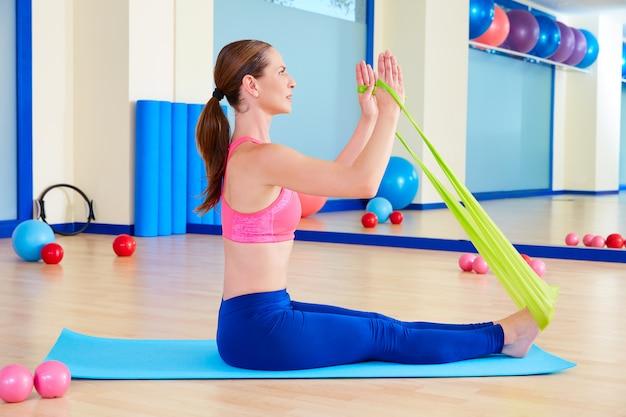 Femme pilates, aviron, élastique