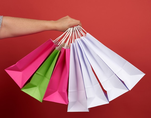 Femme avec pile de sacs en papier sur l'espace rouge