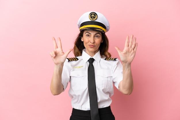 Femme pilote d'âge moyen d'avion isolée sur fond rose comptant huit avec les doigts