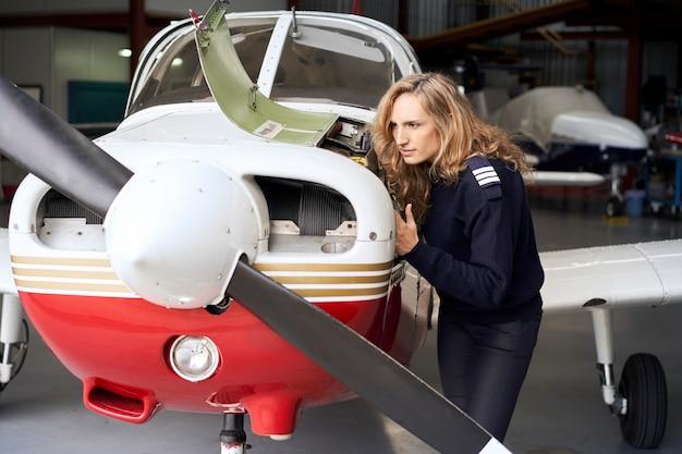 Femme pilote dans le hangar faisant l'entretien du moteur d'un petit avion