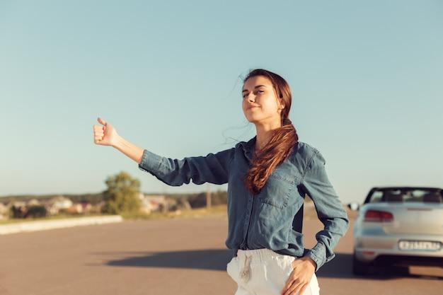 Femme pilote près d'une voiture en panne. une voiture sur une route de campagne, une femme attrape un tour