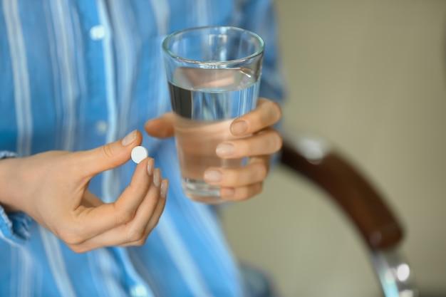 Femme avec pilule et verre d'eau, gros plan