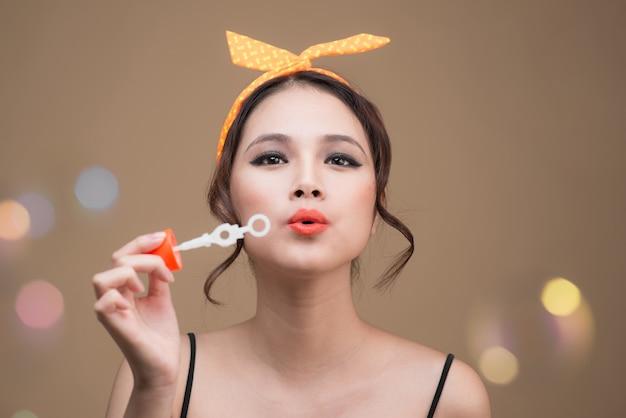 Femme pin-up ludique soufflant des bulles de fête sur fond jaune