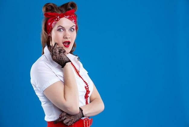 Femme pin-up avec un maquillage lumineux et un bandana presse ses mains sur ses joues de surprise.