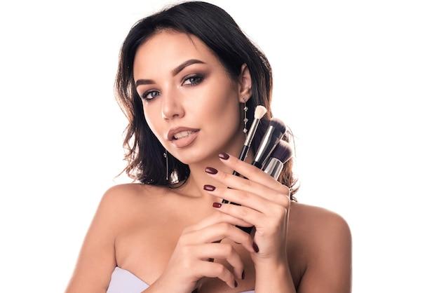 Femme avec des pinceaux de maquillage