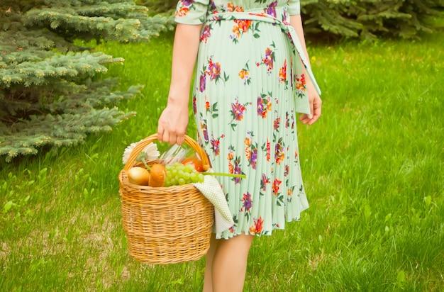 Femme sur le pique-nique se tenir sur l'herbe verte et tient le panier de pique-nique dans une main.