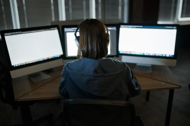 Une femme pirate internet dans les écouteurs fonctionne sur ordinateur dans un bureau sombre. programmeur web illégal sur le lieu de travail, profession criminelle. piratage de données, cybersécurité