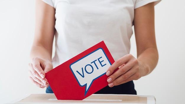 Femme plaçant un carton rouge avec un message de vote dans une boîte