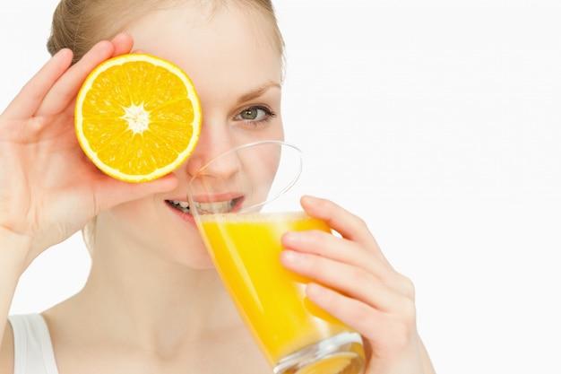 Femme plaçant une orange sur son œil en buvant