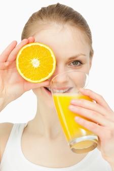 Femme plaçant une orange sur son oeil tout en buvant dans un verre