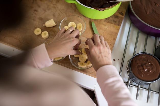 Femme plaçant des tranches de banane dans un bol en verre tout en préparant des desserts individuels dans un angle élevé sur l'épaule des mains.
