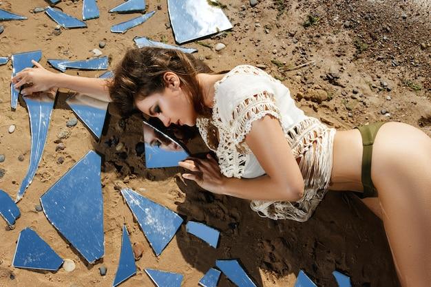 Femme sur la plage avec des éclats de miroir