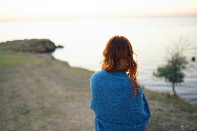 Femme sur le plaid bleu nature admire le voyage du paysage