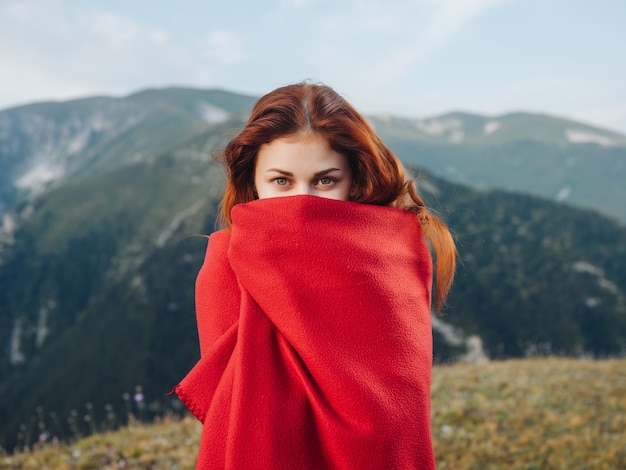 Femme en plaid rouge à l'extérieur posant de l'air frais frais