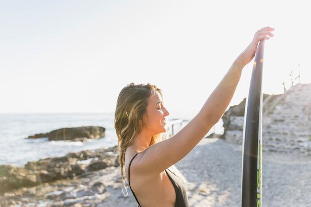 Femme avec planche de surf au bord de la mer