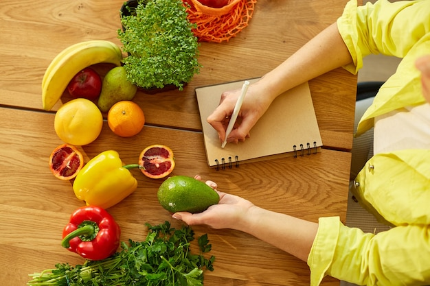 Femme planifiant, écrivant des repas hebdomadaires sur une note de planificateur de repas ou un régime alimentaire sur une table en bois avec des fruits et légumes sains dans sa cuisine à la maison.