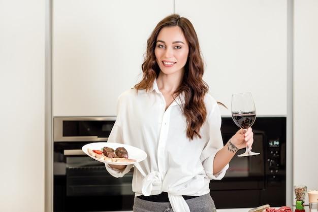Femme avec un plat de viande et du vin rouge à la cuisine