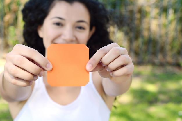 Femme en plein air montrant un bloc-notes vide.