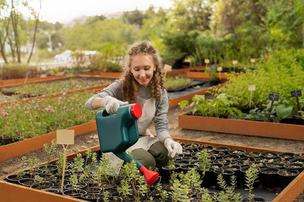 Femme plein coup arrosant les plantes