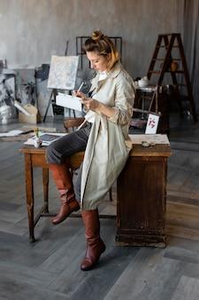 Femme plein coup sur chaise avec tablette
