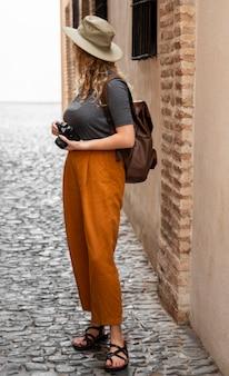 Femme plein coup avec chapeau et appareil photo