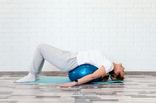 Femme plein coup exerçant avec ballon et tapis