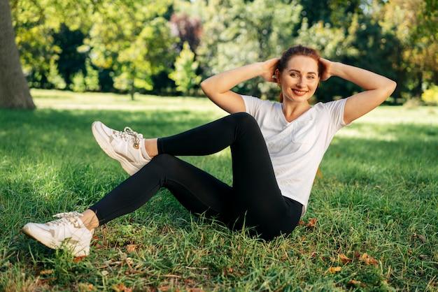 Femme plein coup exerçant sur l'herbe