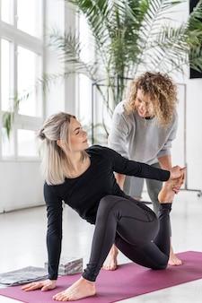 Femme plein coup faisant du yoga à l'intérieur