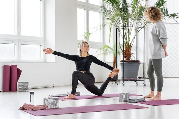 Femme plein coup faisant du yoga avec le professeur