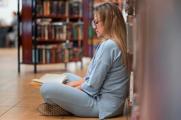 Femme plein coup de lecture à la bibliothèque