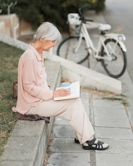 Femme plein coup de lecture à l'extérieur