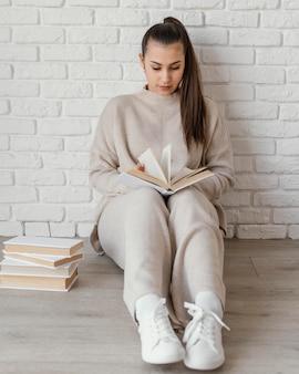 Femme plein coup sur la lecture de plancher