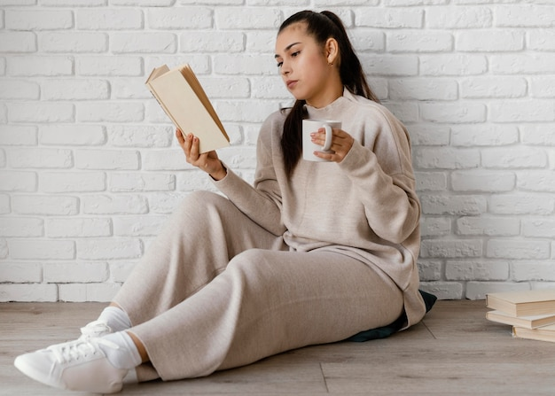 Femme plein coup avec livre et tasse sur marbre