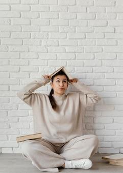 Femme plein coup avec livre sur la tête