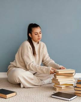 Femme plein coup avec des livres sur le sol