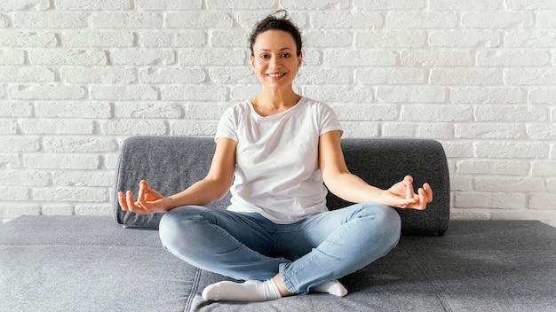Femme plein coup méditant sur le canapé