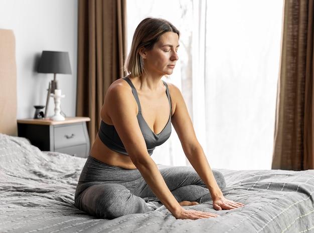 Femme plein coup méditant sur le lit