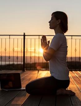 Femme plein coup méditant avec ordinateur portable