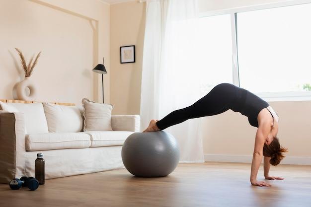 Femme de plein coup s'entraînant avec un ballon de gym à l'intérieur