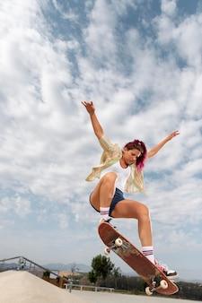 Femme de plein coup sautant avec une planche à roulettes