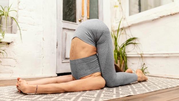 Femme plein coup sur tapis de yoga