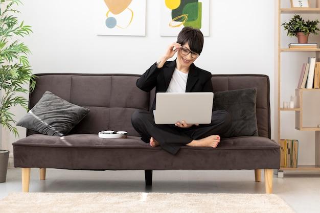 Femme plein coup travaillant avec un ordinateur portable