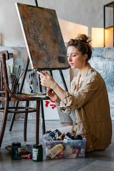 Femme plein coup avec des tubes de peinture