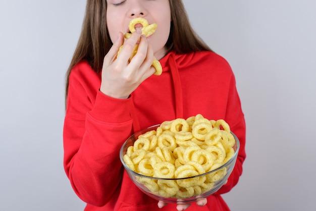 Femme pleine bouche avec des collations tenir la plaque dans la main fond gris isolé